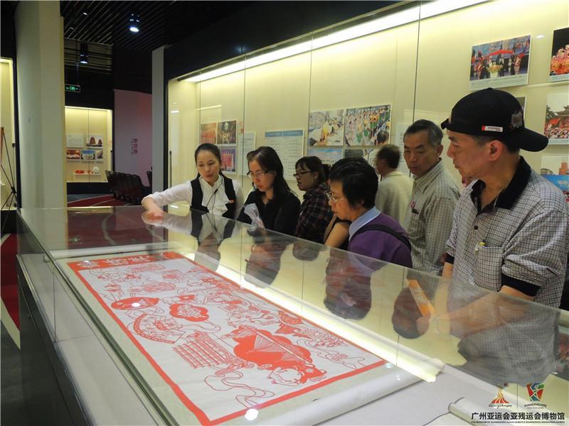 讲解员正在为来自香港的游客讲解关于亚运的剪纸艺术